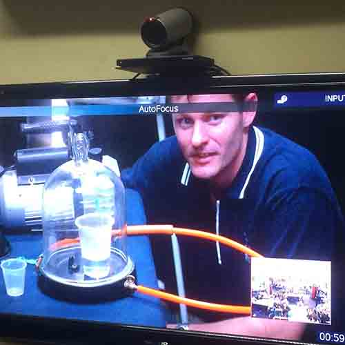 A television screen showing a distance educator running science experiment with a bell jar, vacuum pump and a cup of water. There is an inset of a remote class on the screen and a video conference camera on top of the television.