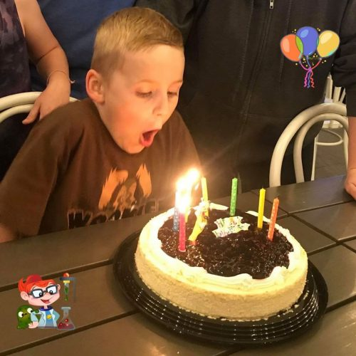 A boy blowing out candles on a cake