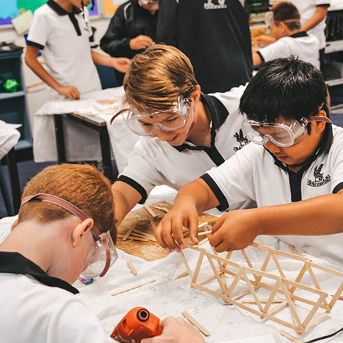 Building bridges with three students working together