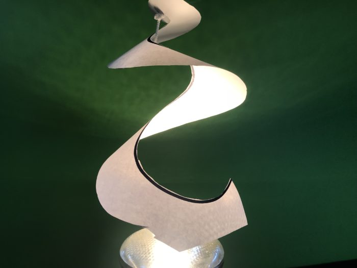 Convection spiral science experiment - spiral paper hanging over the spotlight