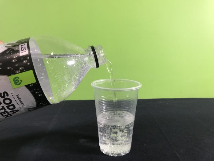 Dancing sultanas science experiment - pouring soda water into a cup