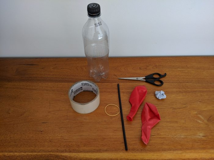 Sticky tape, a black straw, scissors, plastic bottle, blu tak and two red balloons