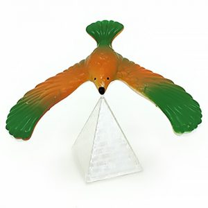 A green and orange balance bird on clear plastic pyramid