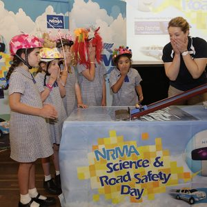 lady with a black shirt showing kids NRMA science & road saftey models