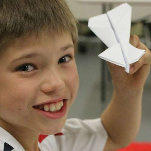 A smiling child holding a paper plane
