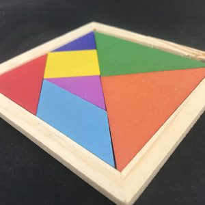 close photo of a Wooden tangram puzzle set in a square