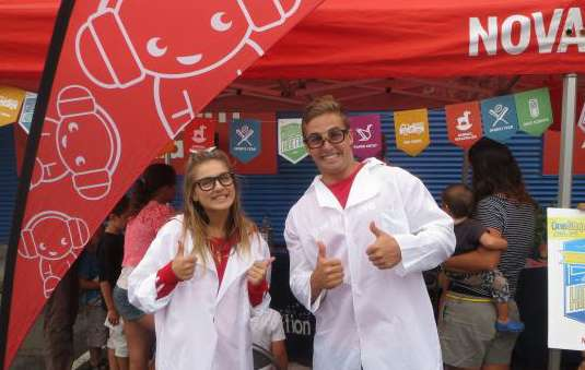 Two people dressed as scientists in front of a Nova science tent