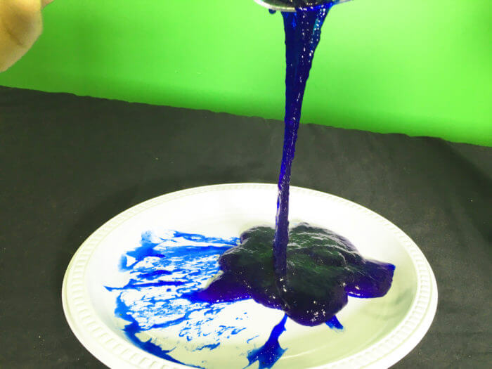 Edible flubber slime science experiment - blue slime dripping off spoon