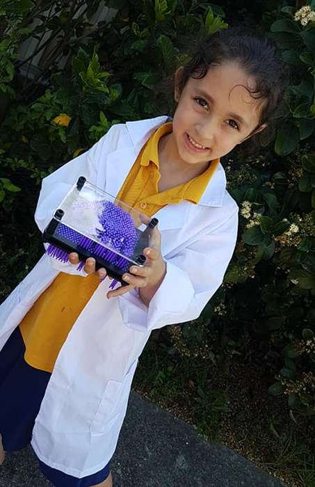 Girl in a lab coat holding a science toy