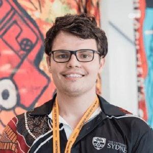 Corey Tutt standing in front of indigenous artwork