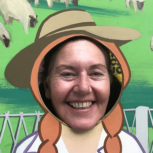 Jenny Hughes from the Royal Agricultural Society of NSW smiling with her head through a farm mural