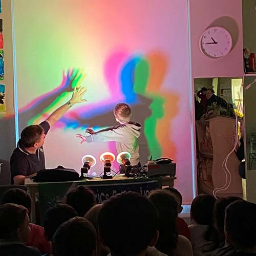 A child standing in front of red, green & blue lights. A rainbow of coloured shadows is behind him on the white curtain blinds