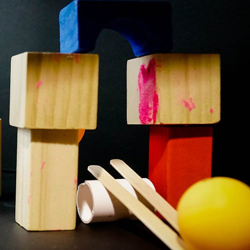 Two paddle pop sticks on a cut PVC pipe with stacked blocks and a ping pong ball