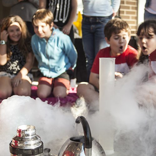 Four kids smiling whilst a fog cloud spills over the side of a science presentation desk past a measuring cylinder, thermos and kettle