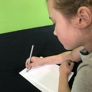 Student using a pen to write on paper on a black table cloth