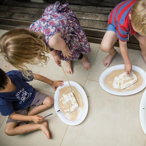 3 children using paintbrushes to sweep sand away from fossil casts