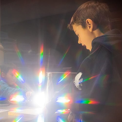 Child surrounded by rainbows created by diffraction glasses