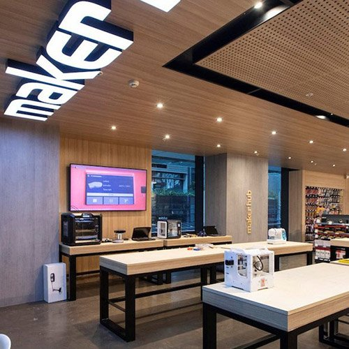 Maker Hub at Central Park Mall, Sydney. The image shows a modern retail space with wood paneling, desks, a 3d printer and a flat screen tv