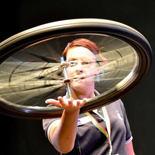Holly balancing a spinning a bike wheel on her hand