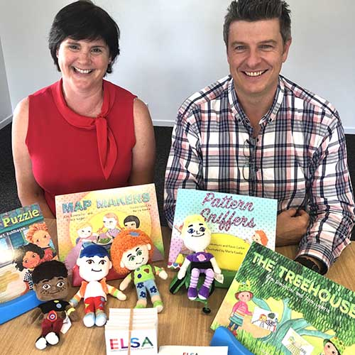 A picture of Matt Bacon and Kym Simoncini sitting at desk with children's books