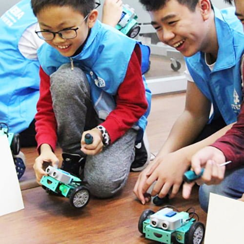 Two students with flip robots on the ground
