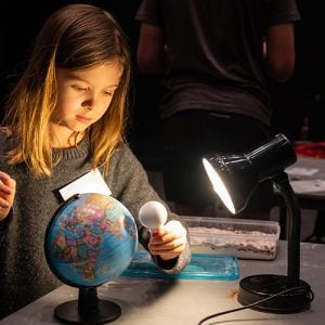 Child with an Earth and moon model