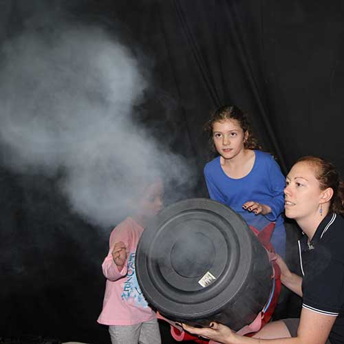 Two kids and Fizzics presenter shootig fog rings our of a bin