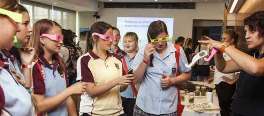 Girls wearing coloured glasses gathered around a table