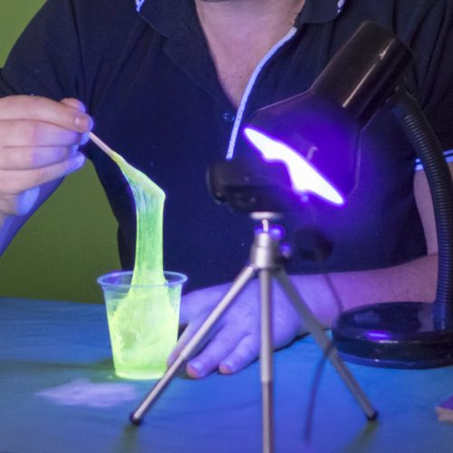 Dripping goeey glowing green slime under a UV lamp and a web cam