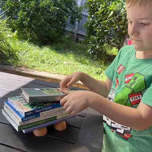 A child adding books onto the eggshells on the table