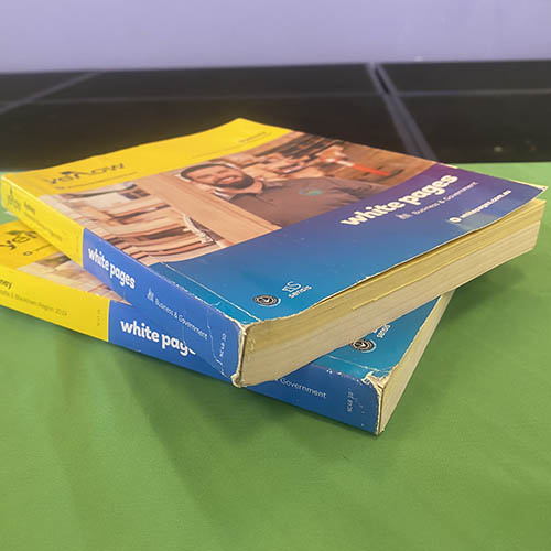 Two telephone books on top of each other on a table