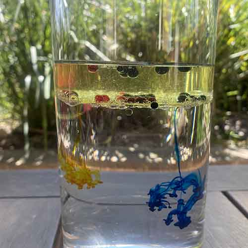 Yellow and blue food colouring falling through water from a layer of oil. The droplets are spreading through the water.