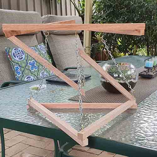 A tensegrity structure made of wood, chains and hooks on a picnic table