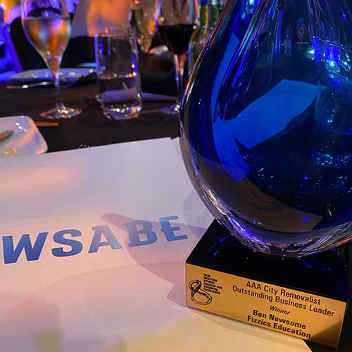 A WSABE Award on a table under the lights - the plaque says AAA City Removalists Outstanding Business Leader of the Year Ben Newsome