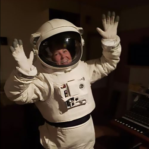 Jacqueline Monteith in a spacesuit  with her hands raised up in the air.