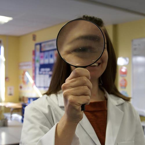 Dr Jo Montgomery holding a magnifier up to her eye. Her eye is very large in the magnifier. She is wearing a lab coat.