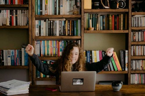 A child sitting a desk with her hands up in celebration whilst looking at a computer. There is a large bookshelf behind her
