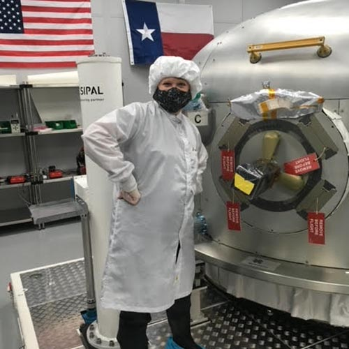 Phyllis Friello dressed in white lab wear with a mask, hairnet and gloves whilst in front of a metal dome with an airlock