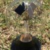 A light bulb shaped glass radiometer with a black plastic base. There are diamond shaped flages inside the bulb (one white and one black). It's on a grassed area