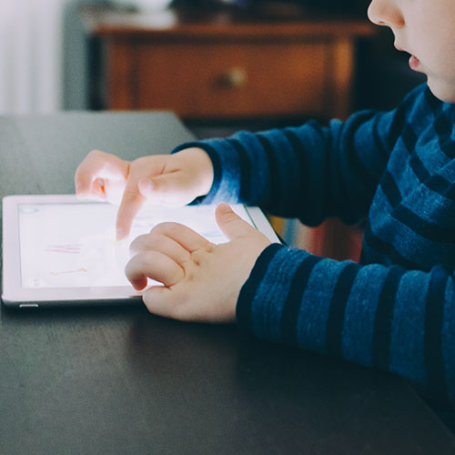 A boy sitting at a desk infron tof a tablet. His hands are touching the screen. Photo by Kelly Sikkema on Unsplash
