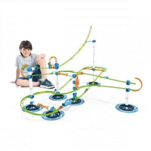 A marble run that looks like a rollercoaster. A boy is sitting behind the marble run