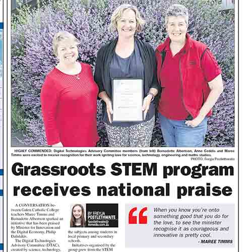 Bernadette, Anne and Maree standing in front of a bush holding an award with the newspaper article title saying 'Grassroots STEM program receives national praise'