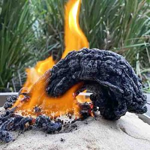 A fire in sand with a black snake-shaped ash column rising out of it and falling to one side