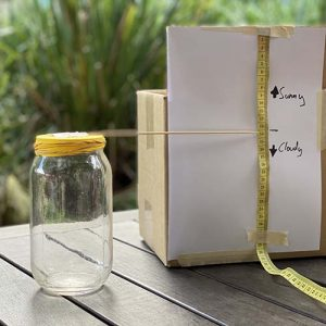 A glass jar with a yellow balloon secured around the opening with rubber bands. A wooden kebab stick is stuck to the balloon and pointing sideways towards a measuring tape that is stuck on a vertically mounted piece of paper. The paper has markings with arrows pointing up and down. The top arrow says 'sunny' and the bottom arrow says 'cloudy'
